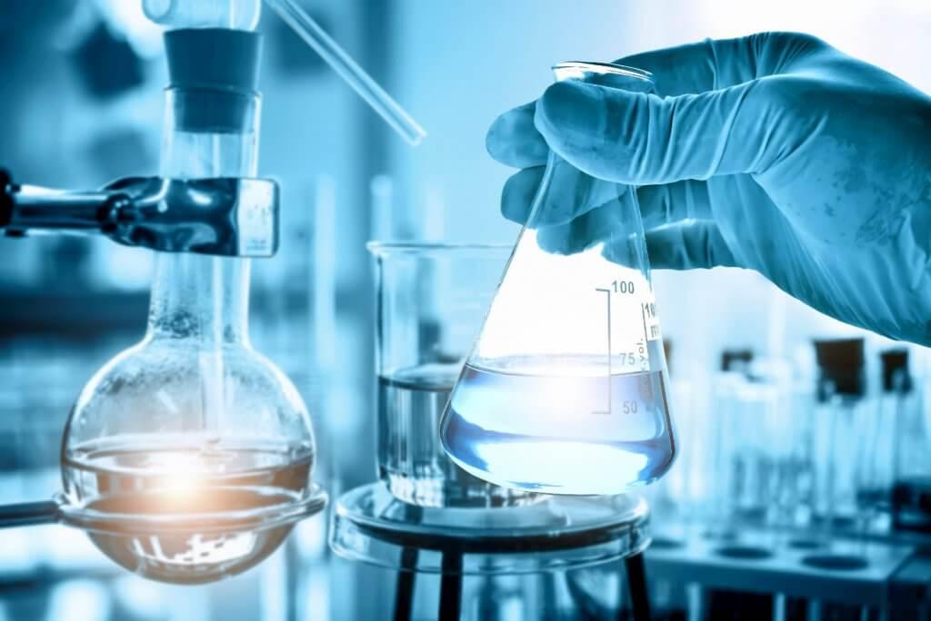 化学実験室の背景、科学実験室の研究開発コンセプトで実験用ガラス器具とフラスコを保持している科学者の手